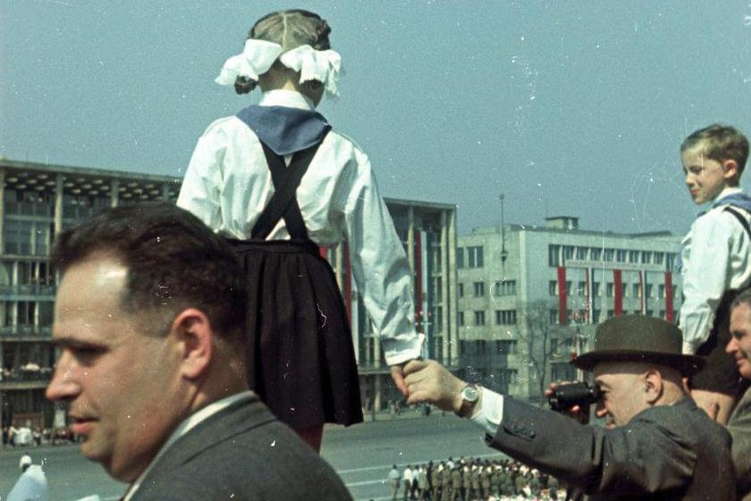 Rákosi Mátyás rakott szoknyás kisdobos kislány kezét fogva figyeli a felvonulókat a dísztribünön 1955. május 1-jén. Fotó: Fortepan.hu