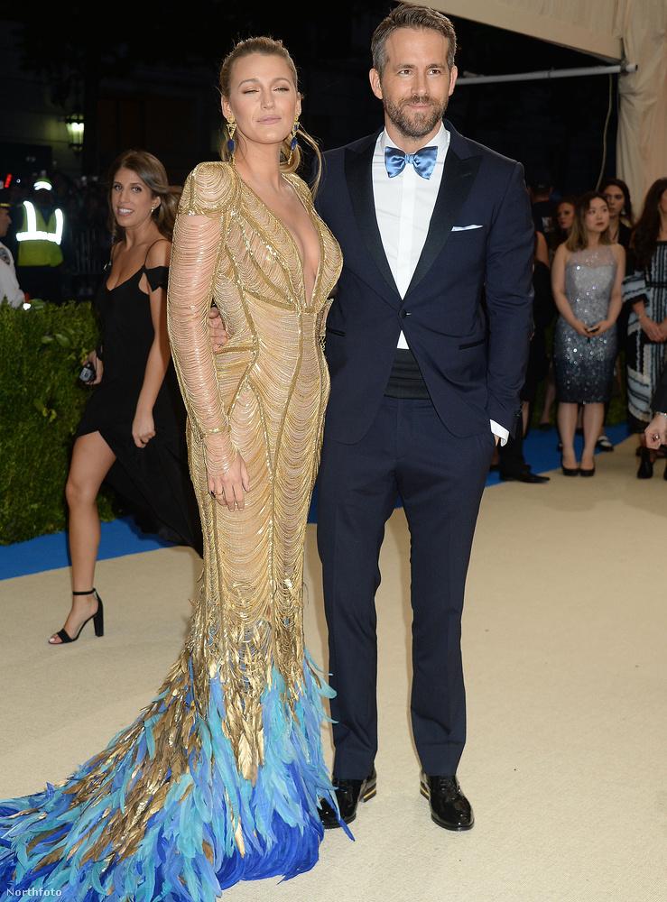 Ryan Reynolds keze felesége, Blake Lively derekán.