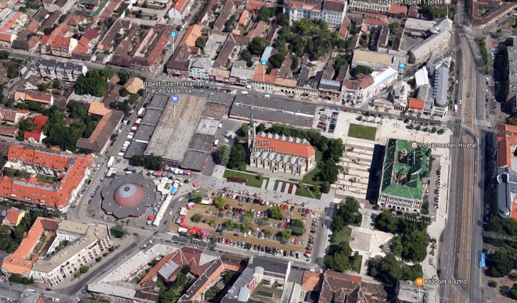 A Szent István tér délről nézve, a Google Maps 2012-es felvételén. Középen a templom, mögötte a városháza, két oldalán a már rendezett térrészekkel. A templommal szemben, és a túloldalán a piac egy-egy csarnoka. A virág alakú épület a Virágpiac. Az új piac a kép bal oldalán látható földszintes házak és a zöld kertek helyére kerül. Cserébe lebontják a mai piacépületeket és oda kerül parkosított tér. Az északi oldalon a buszmegállóval jelzett épület az egykori zeneiskola, ma plébánia. A jobb alsó sarokban a Központ bisztró, ahol remek hamburgert adnak, és ha fehér ingben mész be, egyből hoznak egy plusz szalvétát, amit a nyakadba tűrhetsz, hogy le ne edd magad