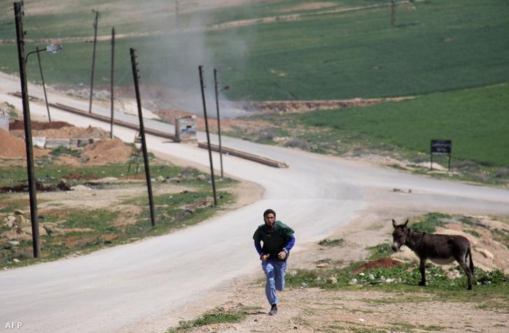 Egy szír orvos fut segítségért a szíraiai Idlib tartományban, miután április 4-én egy kórházat vegyi támadás ért.