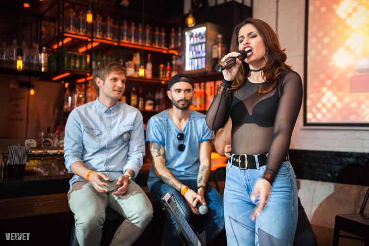 Radics Gigi énekel az X-Faktor sajtóbuliján, Puskás Peti, ByeAlex meg hallgatja.