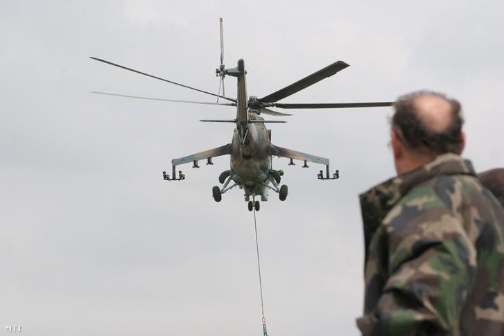 Szekeres Imre honvédelmi miniszter figyeli amint egy MI-24 es harci helikopter repül a Légi Roham 2009 harcászati gyakorlaton az újdörögdi romvárosban.