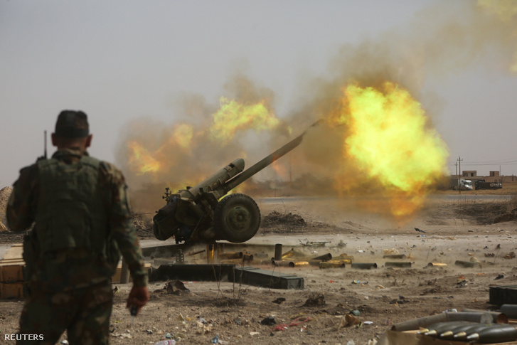 PMU (Népi Mobilizációs Erők) katonák tüzelnek az Iszlám Állam fegyvereseinek kezén lévő moszuli városrészre, a várostól nyugatra fekvő Al-Ba'aj közelében 2017. május 26-án