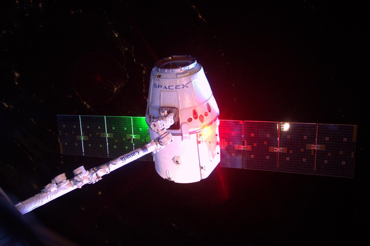 A SpaceX Dragon teherűrhajóját az űrállomás CanadArm karja tartja.