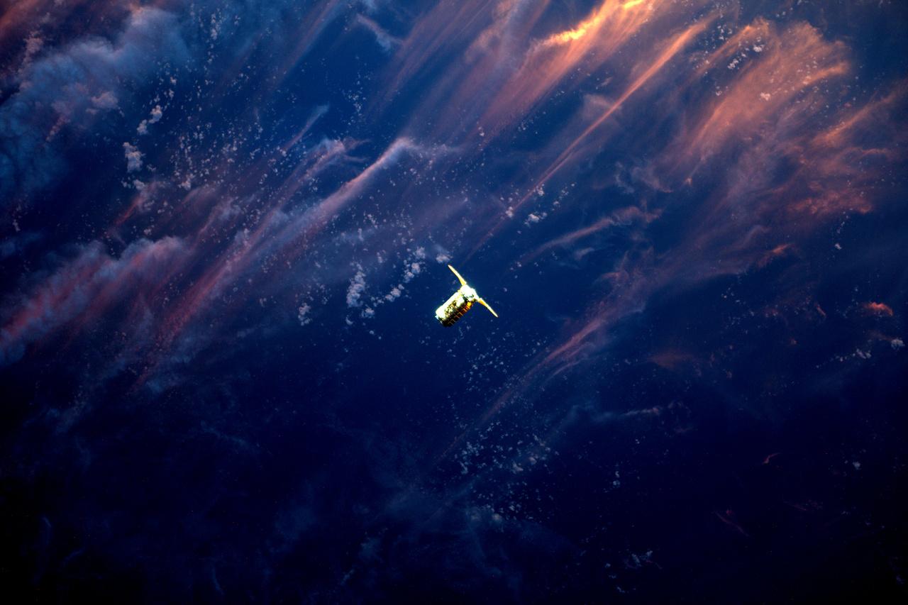Az ISS-ra tartó Cygnus teherűrhajó, földi naplementével a háttérben.