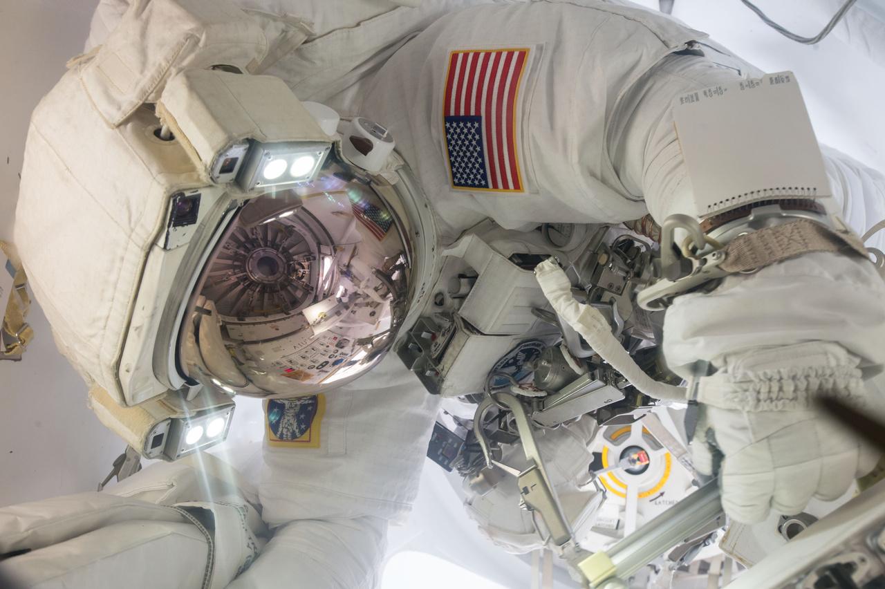 Jack Fischer NASA űrhajós űrsétára készül, sisakjának üvegén a légzsilip ajtaja tükröződik