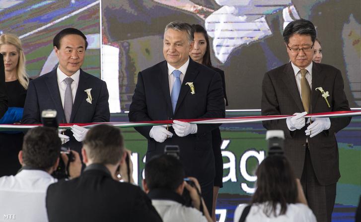 Orbán Viktor miniszterelnök (k) Dzsun Jong Hjun a Samsung SDI vezérigazgatója (b) és Jim Gun Hjong dél-koreai nagykövet átvágja a nemzetiszínű szalagot a Samsung SDI gödi elektromos jármű akkumulátor gyárának nyitóünnepségén 2017. május 29-én.