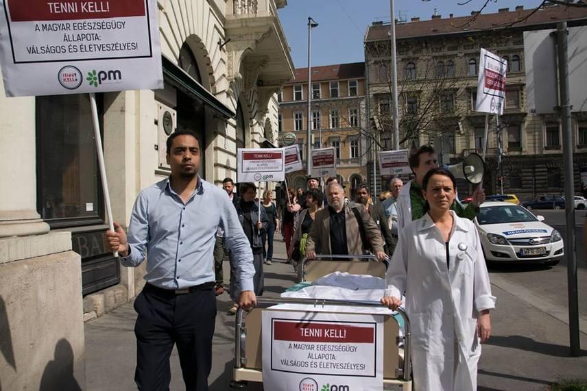 Egy fotó a PM demonstrációjáról: ezt megelőzően Szabó Tímea megkezdte önkéntes munkáját, melynek tapasztalatairól itt számoltunk be. A párt többek között azonnali béremelést kért az ápolóknak és kórházi dolgozóknak, megfelelő feltételeket a kórházi fertőzések megszüntetésére, továbbá azt is, hogy a költségvetés 15%-át az egészségügyre fordítsák a jövőben.