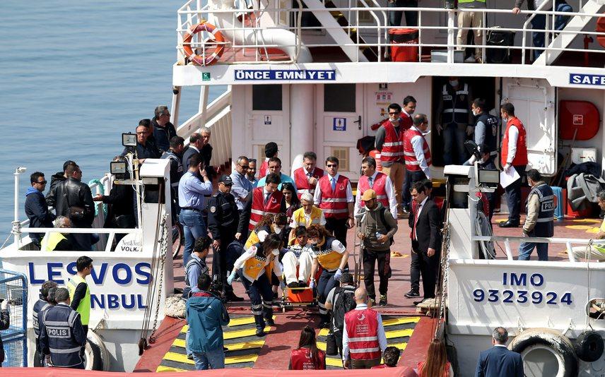 Megérkeznek a migránsok a nyugat-törökországi Izmir Dikili nevű kikötőjébe. Lépéseiket török rendőrök figyelik.