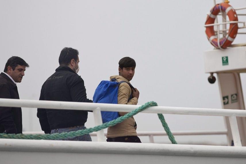 Az Európai Unió határvédelmi ügynöksége, a Frontex egyik munkatársa kísér egy pakisztáni bevándorlót Mitilíni kikötőjében. Pénteken 45 pakisztáni embert vittek el.