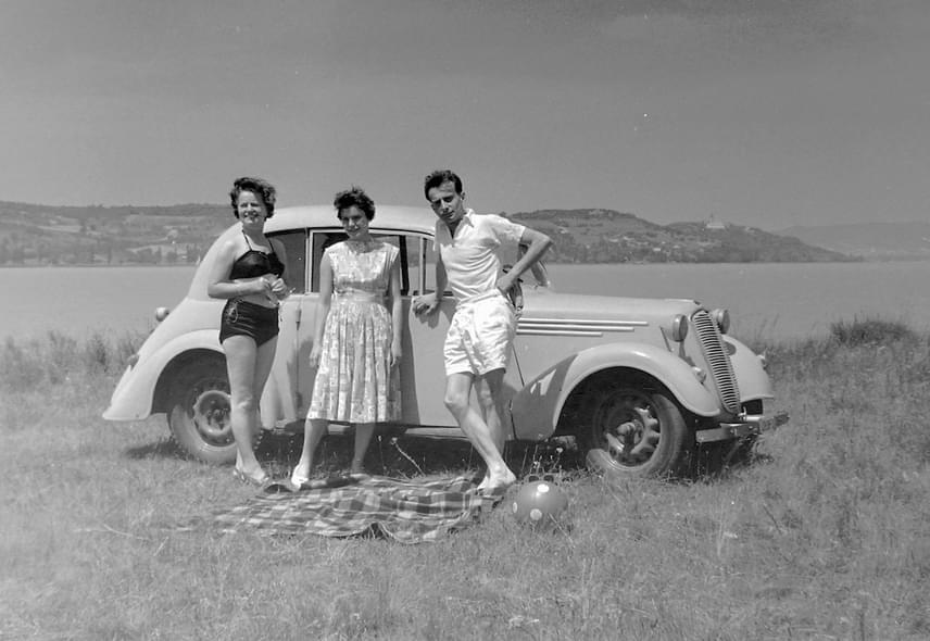 A mosolygós társaság egy Tatra 57B típusú kocsi előtt áll, a háttérben pedig Tihany látható. A fotó 1958-ban készült.