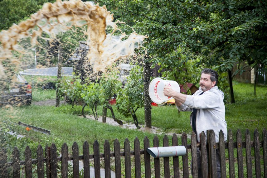 Egy férfi vödörrel meri ki a vizet a kertjéből.