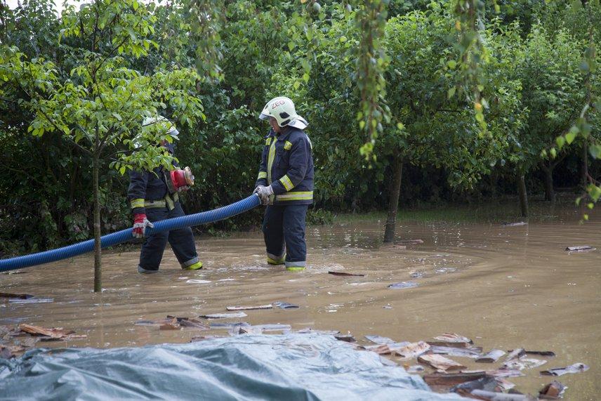 Tűzoltók próbálják elvezetni a vizet Zalaegerszeg Neszele városrészében.