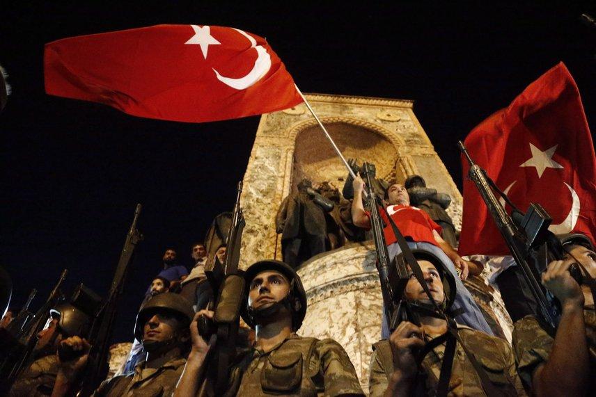 Török katonák őrzik a Taksim teret, a háttérben kormánypárti tüntetők lengetik a nemzeti zászlót.