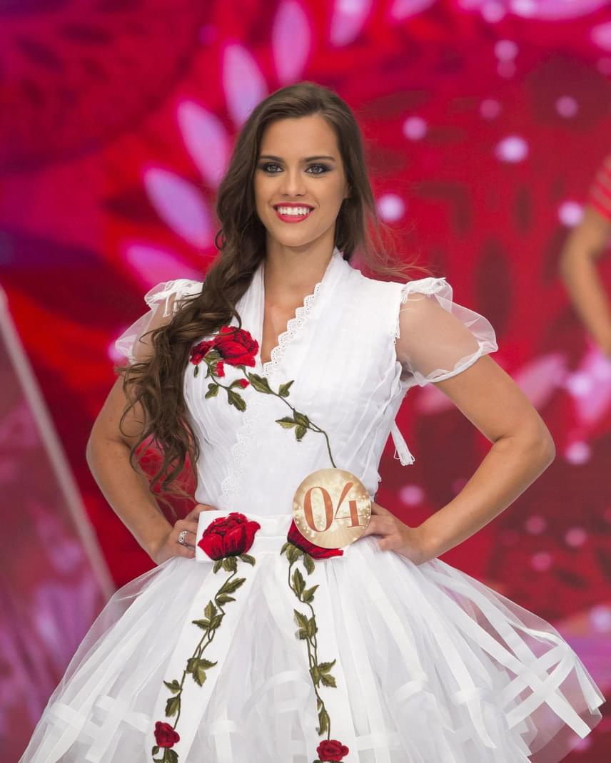 A Magyarország Szépe verseny televíziós döntőjének győztese, Gelencsér Tímea a divattervező és egyben az egyik zsűritag, Bélavári Zita által tervezett, népi motívumokkal díszített ruhában.