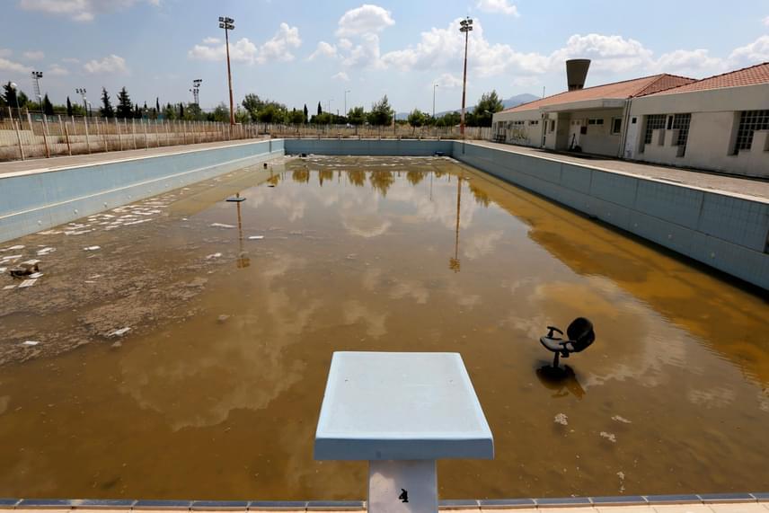 A 2004-es játékok vége óta teljesen kihalt az athéni olimpiai falu. Az edzőmedencében összegyűlt a piszkos, rozsdás esővíz, amelynek kellős közepén bútordarabok hevernek.