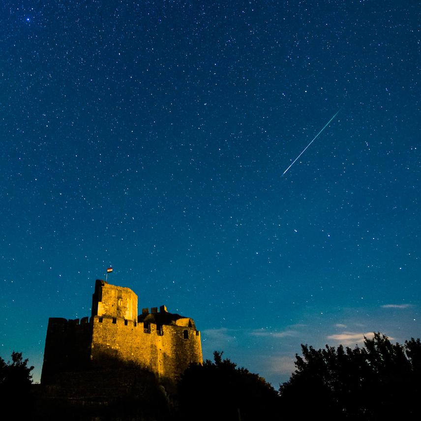 Egy meteor látszik az égbolton a hollókői vár felett 2016. augusztus 12-én. A Föld belépett a Perseida meteorraj összetevőit alkotó 109P/Swift-Tuttle üstökös pályája mentén szétszórt porfelhőbe. Kattints ide a nagyobb felbontású képért!