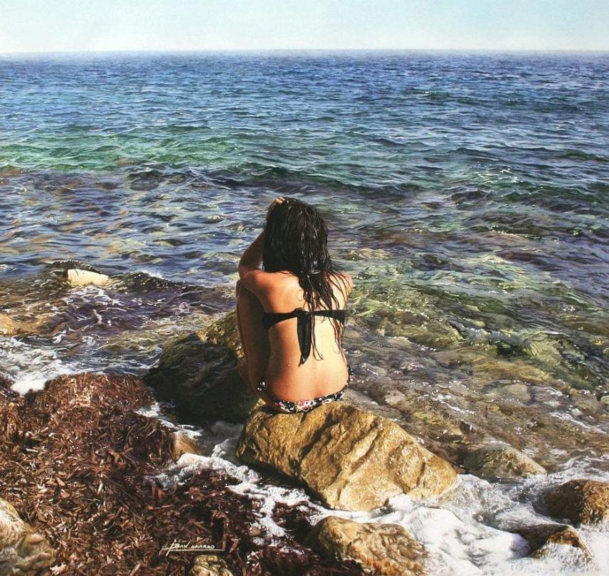 Ez látszólag egy tengerparton sütkérező lány idilli képe. De kitalálod-e, hogy miben más, mint a többi strandot ábrázoló fotó? Eláruljuk: a kép alján, a lánytól picit balra egy apró kézjegyre lehetsz figyelmes: ez Iban Navarro spanyol festő aláírása.A képek titka ugyanis nem kevesebb, mint elkészítési módszerük: elképesztően valósághű, vízfesték alapú festményekről van szó, ez azonban szinte senkinek nem szúr szemet elsőre.