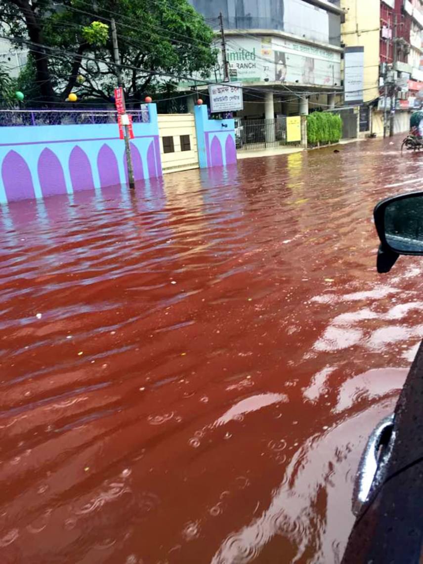 Az autók és a gyalogosok is kénytelenek a bokáig érő véres vízben közlekedni, és az eső még mindig nem állt el.