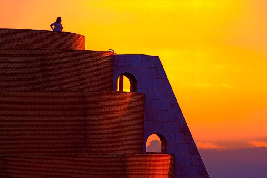 """""""A Sunset Coloratura, vagyis Naplemente koloratúra a Művészetek Palotája melletti kilátóról készült a nyári naplementében. Sok turista és hazai is látogatja, különleges formája miatt egzotikus hangulatot kölcsönöz a városképnek. Boldog vagyok, hogy a világ a verseny révén megcsodálhatja Budapest egy szegletét egy eddig nem látott perspektívából. A fotón egy turista éppen a barátnőjének magyaráz, ő már addigra kisétált a képből"""" - mondja Adrienn."""