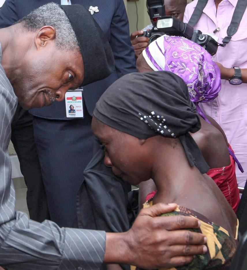 Yemi Osinbajo nigériai alelnök a Boko Haram fogságából kiszabadult 21 diáklány egyikét vigasztalja az elnöki rezidencián tartott fogadáson Abudjában 2016. október 13-án.