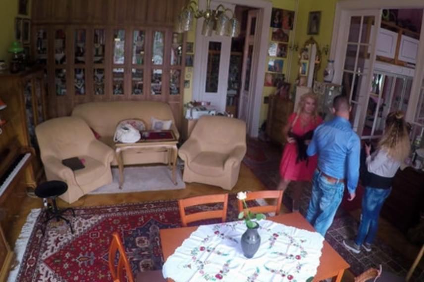 A nappali kicsit zsúfoltnak tűnik: az ülőgarnitúra és az étkezőasztal mellett egy zongora és egy hosszú, üvegezett bútorsor is látható.