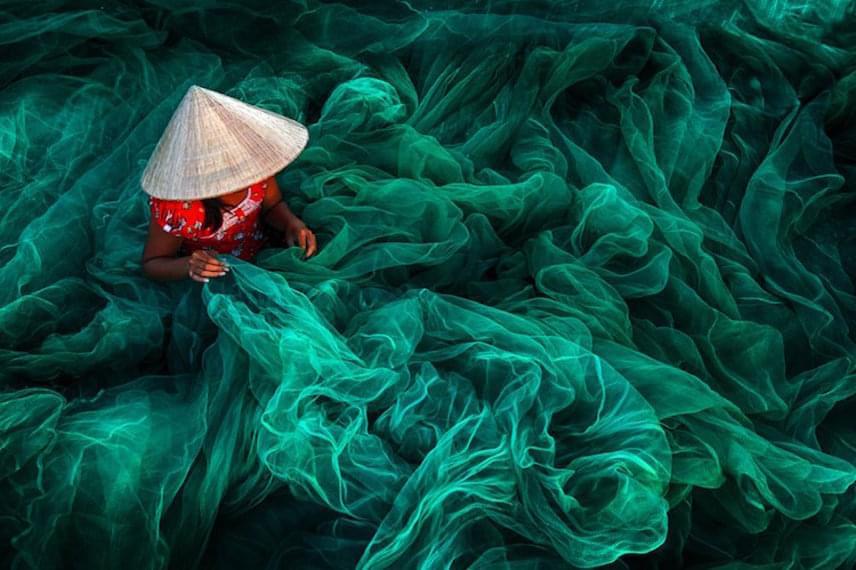 Danny Yen Sin Wong képét szintén nyertessé választották a színes felvételek között. A Vietnamban készült fotóazt mutatja meg, amint egy halászfaluban élő asszony pompás színek ölelésében épp egy halászhálót készít.