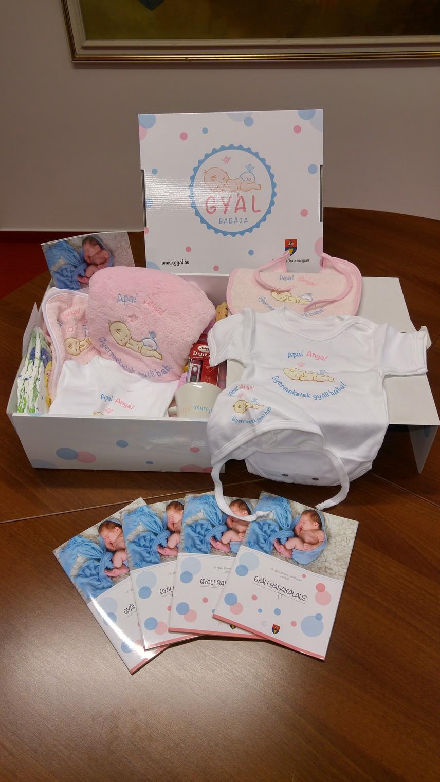 """A csomagban van egy csomag pelenka, digitális hőmérő, takaró, törülköző, 62-es méretű body, 74-es méretű body, partedli, sapka, textilpelenka, és egy darab bögre """"Anyuka vagyok"""" felirattal. Ezek mellett egy anyukáknak szóló kiadvány is kerül a babacsomagokba."""