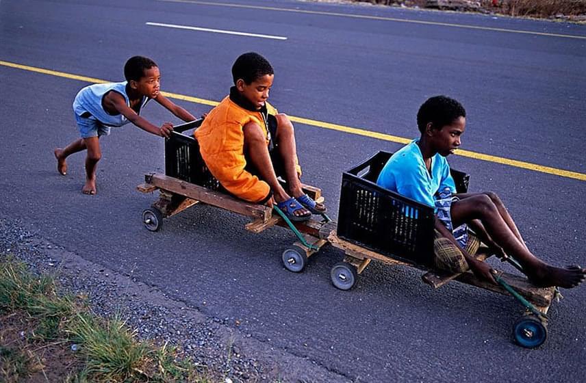 Ládákból eszkábált kiskocsikkal játszanak a dél-afrikai gyerekek. Ugyan a legkisebb tolja a nagyobbakat, maga a játék egyszerű, mégis örömteli.Fotó: Tino Soriano