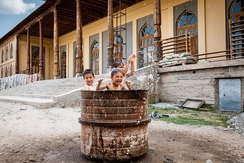Nemcsak vízforgatós kerti medencében, hanem rozsdás hordóban is lehet ilyen gondtalan a pancsolás. (Tadzsikisztán)                         Fotó: Damon Lynch