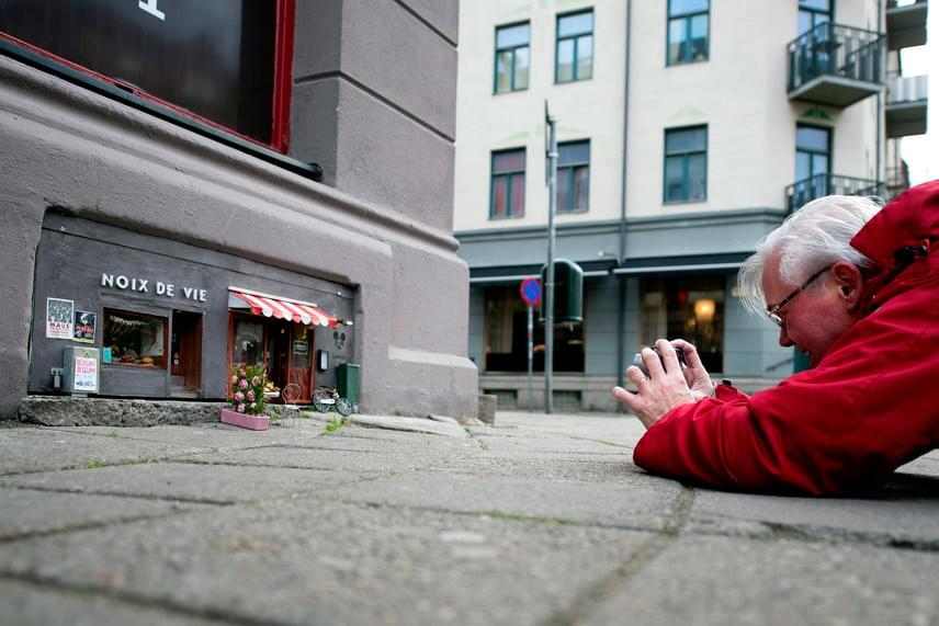 A járókelők körében nagy sikert aratott a kis remekmű: ez a férfi még a járdára is lehasalt, hogy lefotózza a kis éttermet.