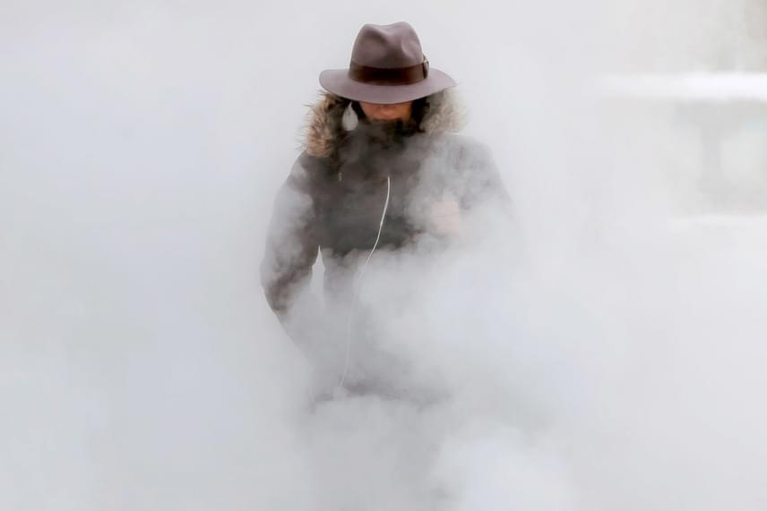 Tél Romániában: föld alatti szellőztetőből feltörő gőzfelhőben egy nő Bukarestben 2017. január 10-én, amikor a levegő hőmérséklete -20°C alá süllyedt a román fővárosban.