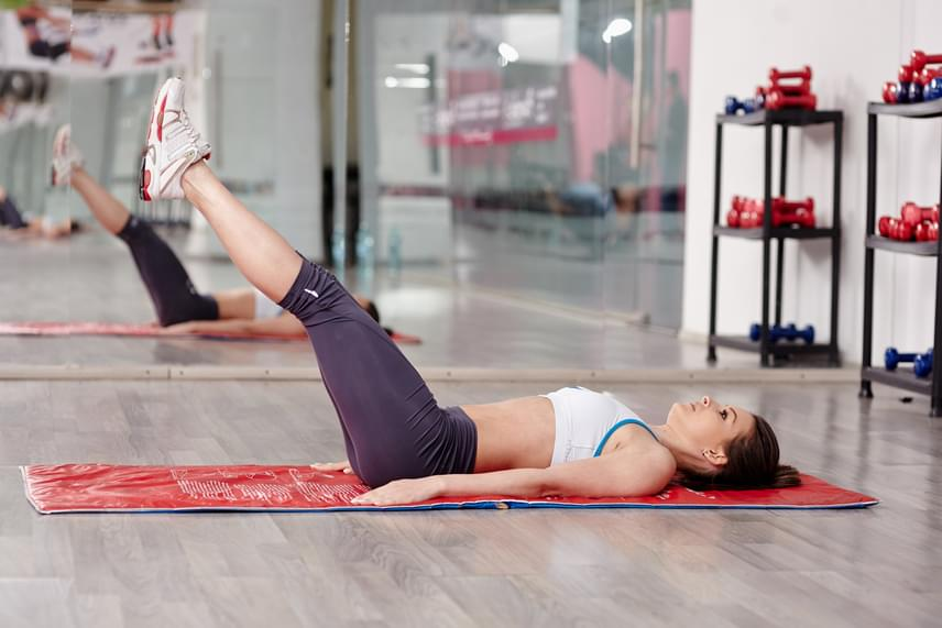 Az alsó hasizmok erősítéséhez feküdj hanyatt, tartsd a tested mellett lefelé fordítva a kezedet, nyújtsd ki párhuzamosan a lábaidat, majd ezeket egyenesen tartva hasból emeld fel őket körülbelül a képen látható szögig. Innen engedd vissza a lábaidat, míg nagyjából nincsenek tíz centire a talajtól, majd emeld vissza őket újra. Ismételd a gyakorlatot 30-szor, majd tarts egy perc pihenőt.