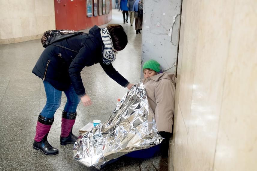 Pászka Petra banki munkatárs egy hőtartó takarót, izolációs fóliát ad egy rászorulónak Budapesten, a Nyugati téri aluljáróban 2017. január 12-én.