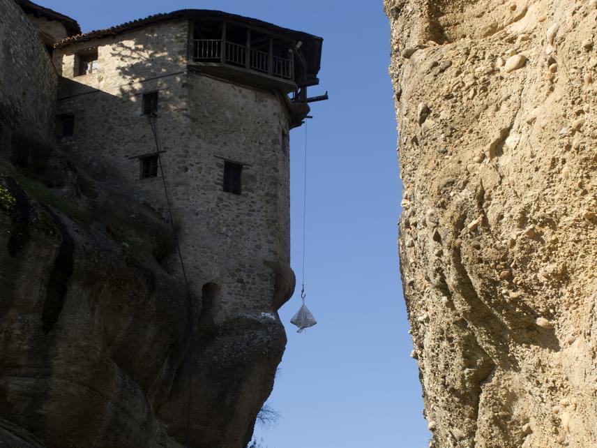 A meteora-oszlopok barlangjaiban már évezredekkel ezelőtt is laktak emberek, ám az aszkétikus szerzetesek csak a 9. században kezdtek letelepülni a sziklás vidéken. Az első, a 11-14. században épült kolostorokat azért hozták létre, hogy a hódító törökök és a politikai viszályok elől menedékre leljenek. Erre tökéletes lehetőséget biztosítottak a magasban épült kolostorok, melyeket csak a képen láthatóhoz hasonló kötélen húzott hálóban, kivételes mászóügyességgel vagy könnyen eltávolítható létrákkal lehetett megközelíteni.