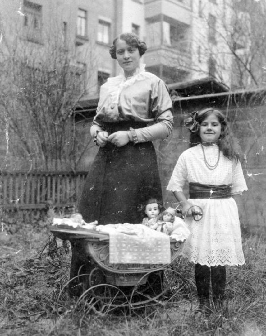 A boldog békeidőkben, 1920-ban készült ez a kép, melyen csipkeruhába öltözött, selyemmasnis kislány feszít anyukája vagy nevelőnője mellett. A vékony, ringó kerekű, küllős babakocsi óriási érték volt akkoriban a gyerekeknek.