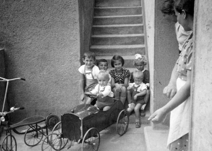 1935-ben így nézett ki egy bölcsőde. Az udvari foglalkozásnál népszerű kinti játékok álltak az aprónép rendelkezésére. Ilyen volt a kis pedálos bádogautó és a roller. A kisebbeknek triciklit, a nagyobbaknak kétkerekű kerékpár készített ki a dajka.