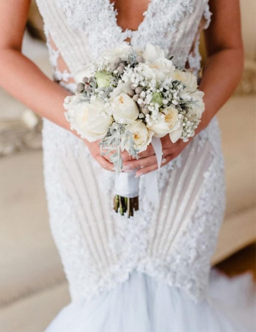 A menyasszony egy merész, de klasszikus, hófehér, csipkével díszített ruhát választott, amihez gyönyörű csokor készült.