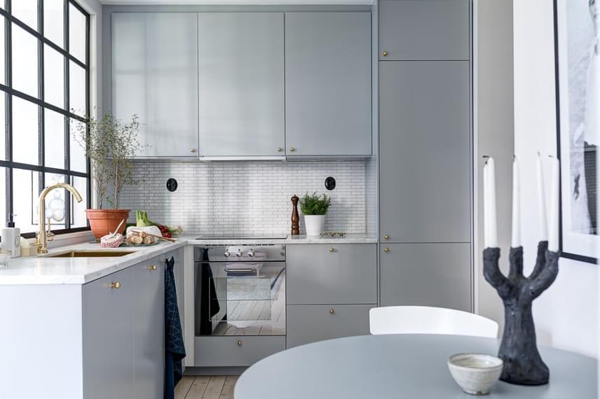 A konyha szintén nem túl nagy, mégsem tűnik zsúfoltnak: az, hogy az ebédlőasztalt nem teljes mértékben a konyhában helyezték el, a térérzetet is növeli, emellett egyszerre jelent átmenetet és elválasztóvonalat a helyiségek között.