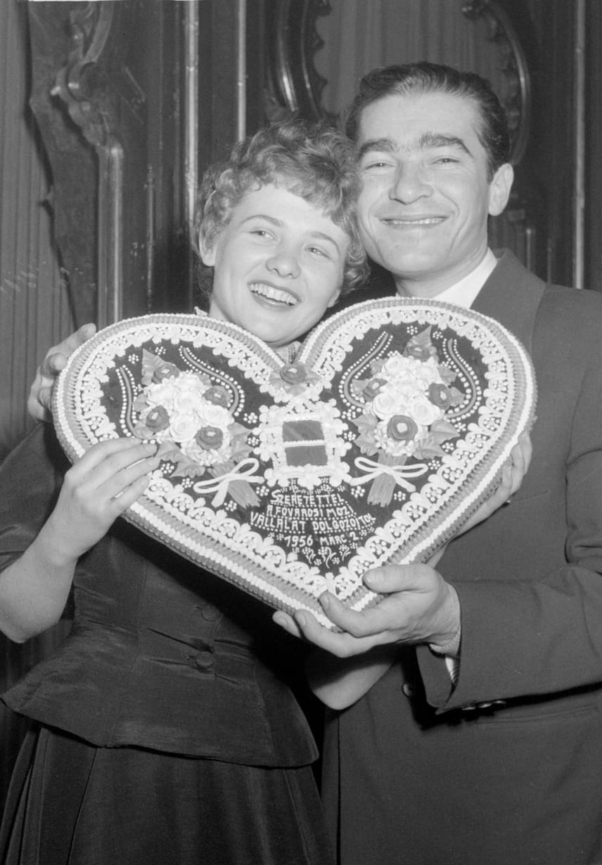 """Törőcsik Mari és Soós Imre kezükben mézeskalács szívvel a Körhinta című film ősbemutatóján az Uránia Filmszínházban 1956. március 2-án. Fábri Zoltán Arany Pálmára jelölt klasszikusa Törőcsik Mari első filmje volt, amiben Soós Imre utolsó előtti mozgóképes alakítását láthatjuk. Törőcsik Mari csak tavaly árulta el, hogy Soós Imrével """"kicsit egymásba is szerettek"""", ez közös fotójukon is érződik."""