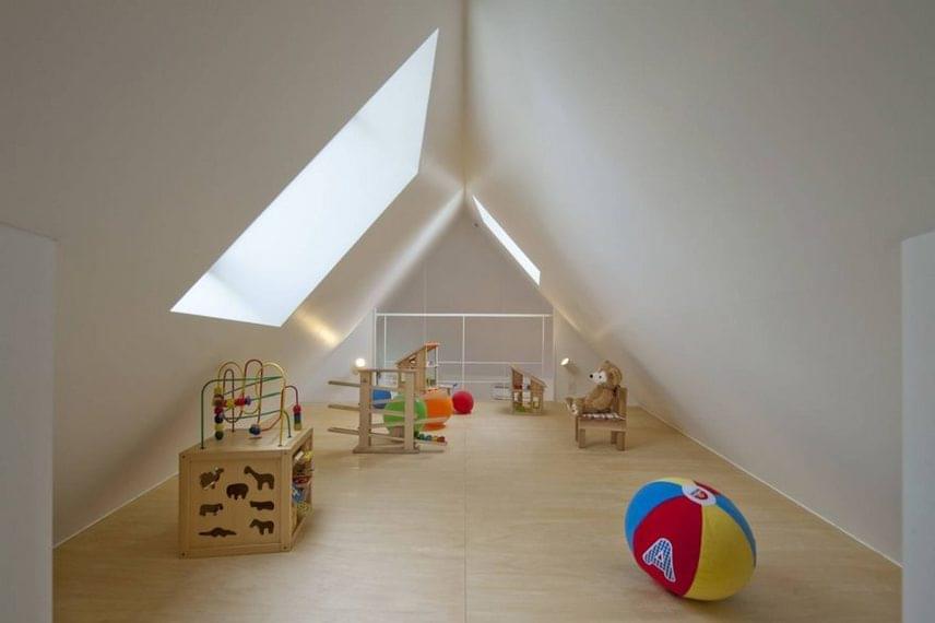 A tetőtér duplikált ablakai, a természetes színű pasztell faburkolat és a hófehér falak tágasság és szabad tér érzetét keltik.