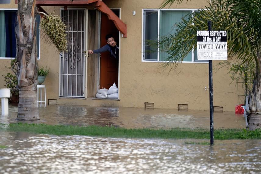 Egy helyi lakos nézi az egyik elöntött utcán hömpölygő vizet 2017. február 21-én. A környékbeliek homokzsákokkal védik a bejárataikat, hogy ne jusson be az otthonukba az áradat.