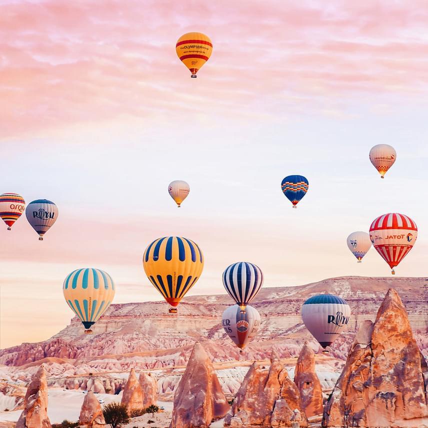"""A sziklákból kiálló """"tündérkémények"""" és az egész vidék lélegzetelállítóan néz ki a hőlégballonokból is. A föld alatt pedig több mint nyolcemeletnyi terület található, egész városokat alakítottak ki a barlangrendszerben."""