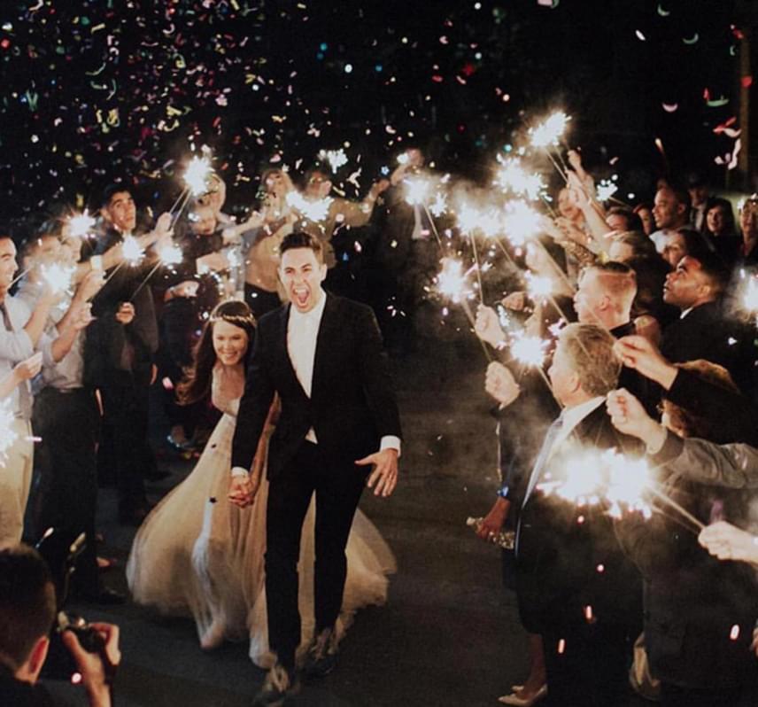 A fotó spontaneitása, hogy még az esküvői fotós is szerepel a képen. A képen átütő a friss házasok érzelemvilága. A hihetetlen öröm, amit a férj arca tükröz.