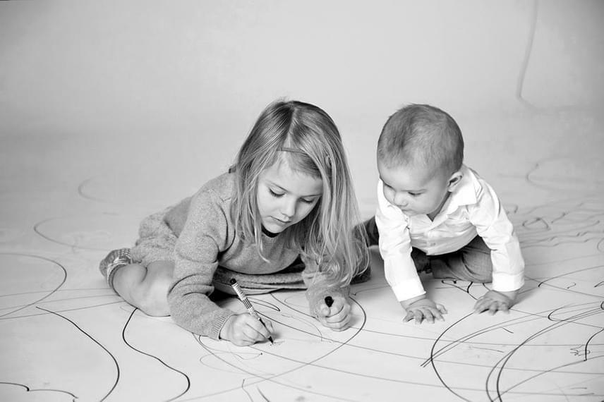 Egy hatalmas papírvásznat feszítettek ki a padlóra, hogy rajzolhassanak rá a gyerekek. Estelle öccse, Oscar herceg buzgón figyeli, mit alkot a nővére.