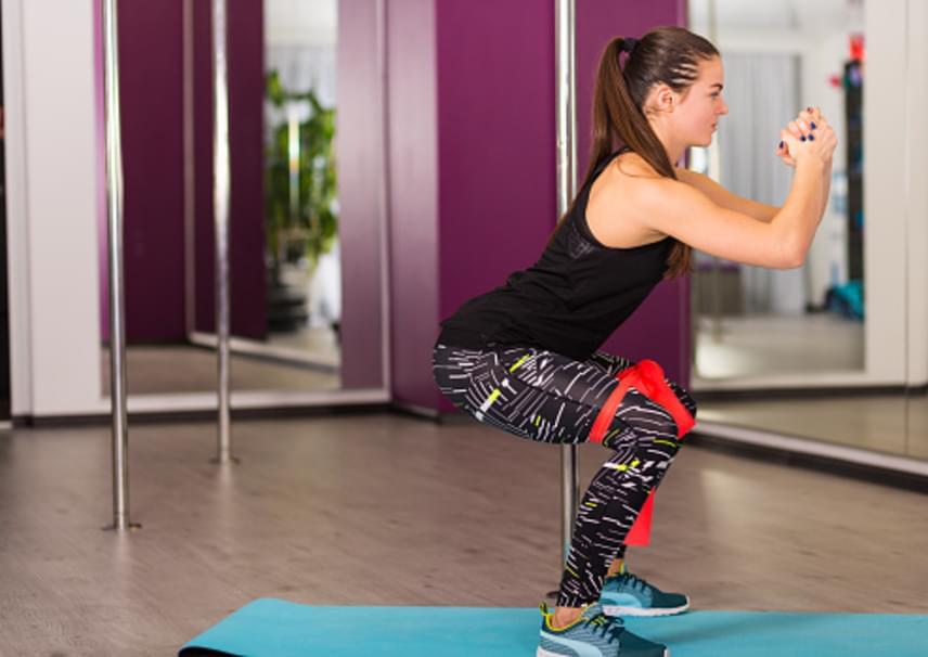 Köss a térded fölé nagyjából tíz centivel közepes vagy erős gumiszalagot úgy, hogy a térdeidet kényelmesen 30 centire tudd nyitni egymástól. Végezz így, összekötött térdekkel guggolást egyenes háttal, a térdedet a lábfejed mögött tartva. Maradj guggolásban öt másodpercig, majd emelkedj fel. Egy sorozatba 15 guggolás tartozik, ami után tarts 30 másodperc pihenőt. Kezdj három sorozattal, majd növeld a sorozatszámot heti eggyel vagy válts egy fokozattal erősebb szalagra, ha könnyűnek érzed a gyakorlatot.