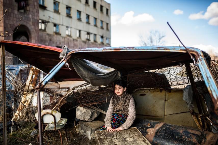 A kilencéves Syuzanna egy rozsdás autóroncs alatt bujkál egy elhagyott lakóház előtt, az örményországi Gjumri városában. A fotót az örmény Yulia Grigoryants készítette, Mindennapi élet kategóriában.