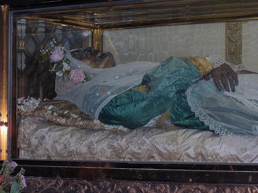 Szent Zita egy szegény olasz családban született az 1200-as években. Szülei cselédnek adták egy családhoz, akiknél egész életében szorgos munkát végzett. Belépett a ferences III. rendbe, megtanult írni-olvasni. Legendái között feljegyeztek egy olyan alkalmat, amikor a vándornak adott kútvíz borrá változott, egy koldusnak pedig köpenyét adta oda. 1696-ban avatták szentté, mára a háztartásban dolgozók és a pincérek védőszentjeként tisztelik.