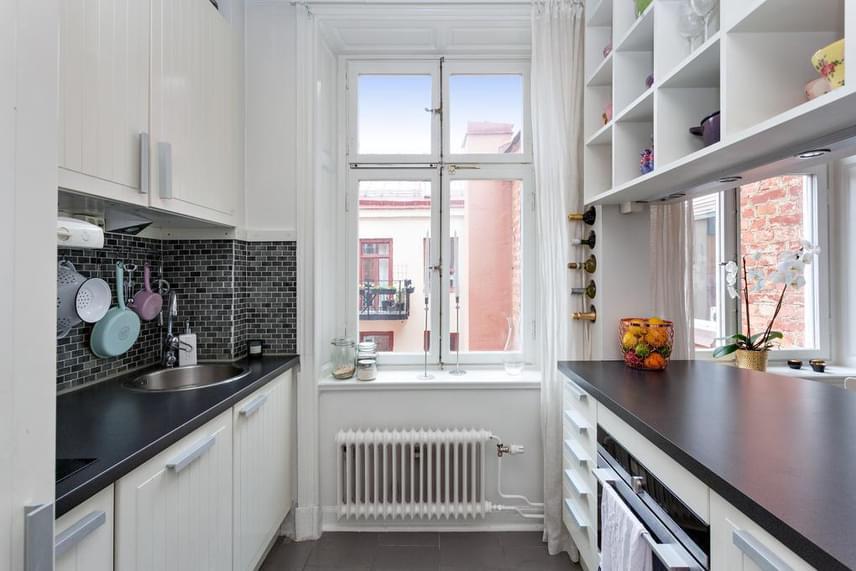A konyha egyszerű és praktikus, ami a lakás egészére is igaz. Mégsem unalmas, köszönhetően többek között a dekorációk és kiegészítő eszközök lágy színeinek és az apró részletek finomhangolásának.