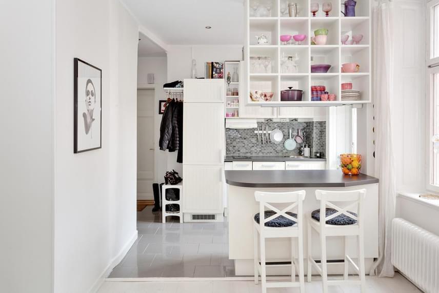 A konyhapult asztalként és térelválasztóként is funkcionál, amit tökéletesen kiegészít a fölötte elhelyezett sokrekeszes polcfelület, ami az ágyhoz hasonlóan kiváló példa arra, hogy nem csak a vízszintes felületek és a falak mentén érdemes gondolkodni, ha plusz helyre van szükség.